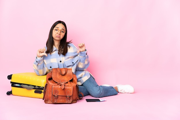 Reiziger vrouw met een koffer zittend op de vloer met duim omlaag met twee handen
