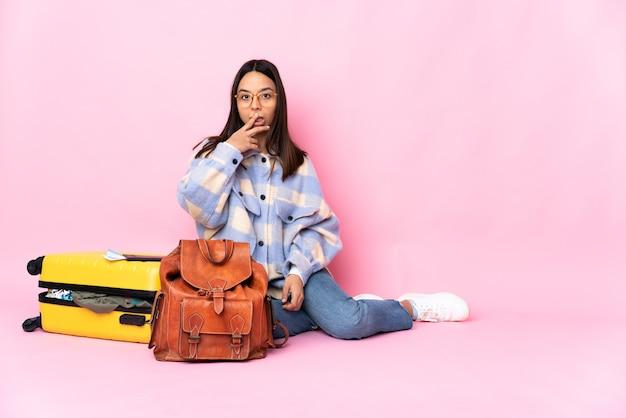 Reiziger vrouw met een koffer zittend op de vloer