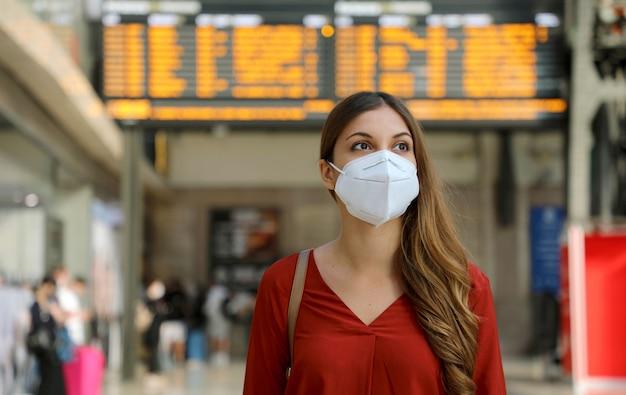 Reiziger vrouw met kn95 ffp2 gezichtsmasker op treinstation ter bescherming tegen virussen en smog.