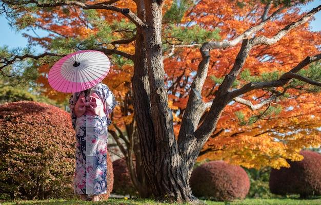 Reiziger vrouw met paraplu in het park, achteraanzicht, herfst esdoorn bladeren reizen concept.