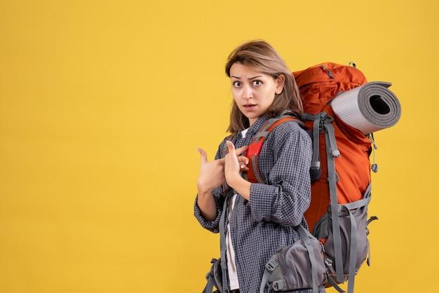 Reiziger vrouw met rode rugzak wijzend op zichzelf