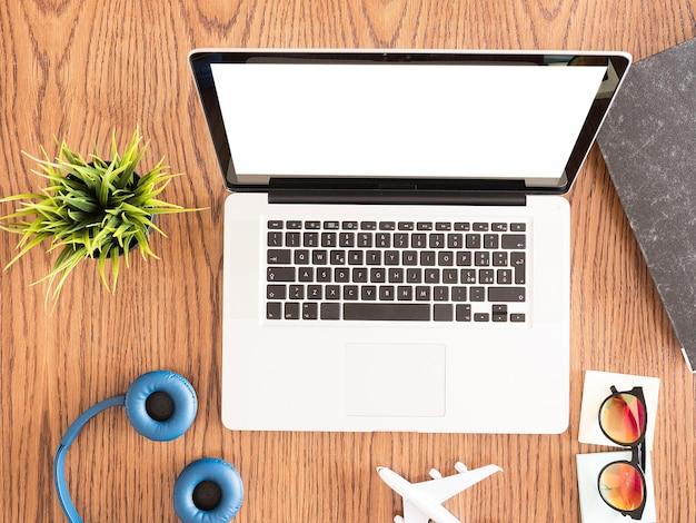 Reiziger zakenman laptop op houten bureau wedijveren, zonnebrillen, koptelefoons, boek
