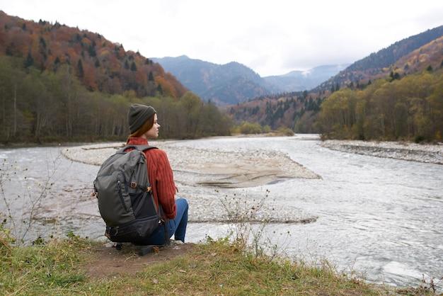 Reiziger zit aan de oevers van de rivier in de bergen in de natuur