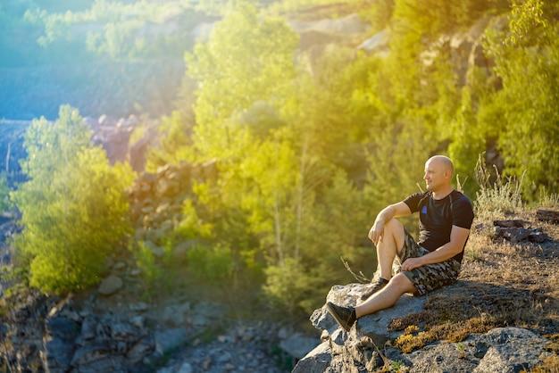 Reiziger zit en geniet van nature om hem heen op een klif.