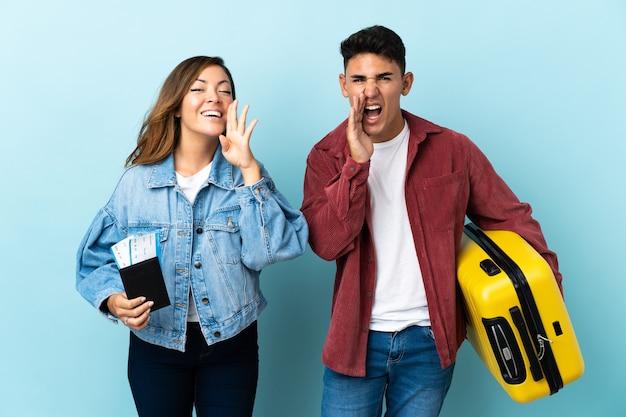 Reizigerpaar dat een koffer op blauw houdt dat en iets aankondigt