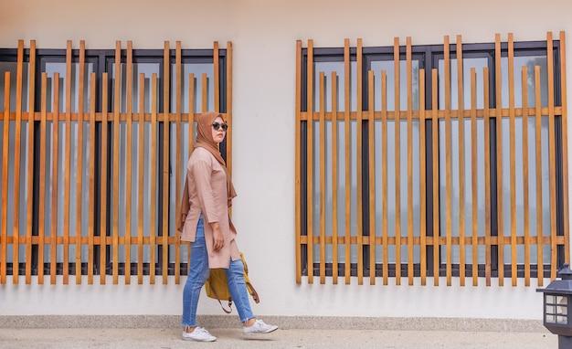 Reizigers aziatische moslimvrouw die bij achtergrond lopen