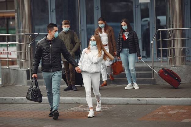 Reizigers die de luchthaven verlaten, dragen beschermende maskers