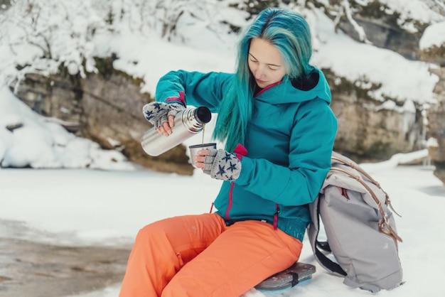 Reizigers gietende thee aan kop in de winter