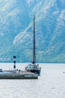 Reizigers hielden een huwelijksceremonie aan de oever van de baai van boko-kotskoy op de achtergrond van een luxejacht.