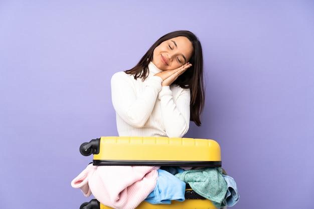 Reizigers jonge vrouw met een kofferhoogtepunt die kleren slaapgebaar in aanbiddelijke uitdrukking maken