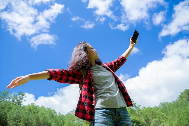 Reizigers, jonge vrouwen, kijken naar de geweldige bergen en bossen, reislustige reisideeën, ruimte voor berichten, geweldige momenten van de atmosfeer.