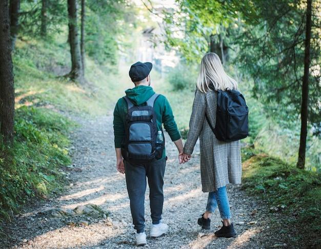 Reizigers paar verliefd genieten in het bos. vrijheid en actieve levensstijl concept. achteraanzicht