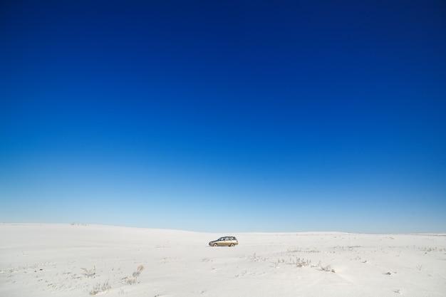 Reizigersauto op besneeuwde weg.