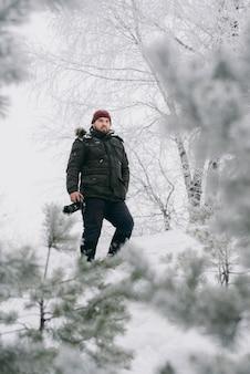 Reizigersfotograaf die foto's in het de winterbos nemen