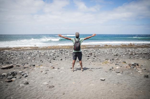 Reizigersjongen op het strand opent zijn armen en kijkt naar de lucht, hij geniet van zijn reis en is gelukkig. reiziger concept.
