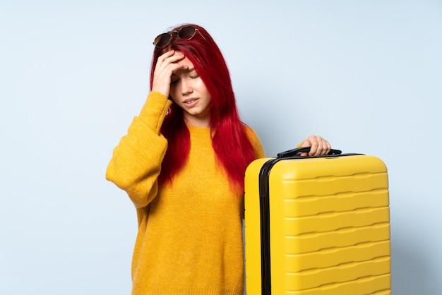 Reizigersmeisje die een koffer houden die op blauw met hoofdpijn wordt geïsoleerd