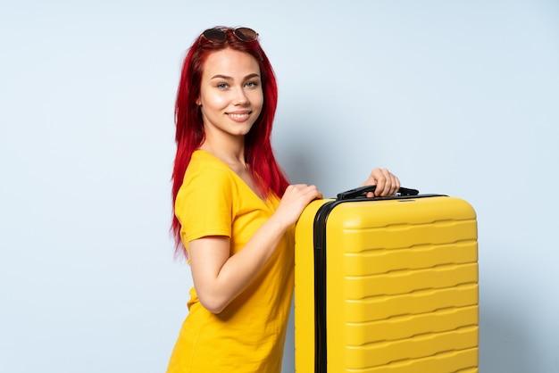 Reizigersmeisje die een koffer op blauwe achtergrond met gekruiste wapens houden geïsoleerd en vooruit eruit zien