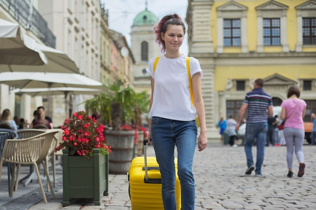 Reizigersmeisje die met rugzak en gele koffer lopen