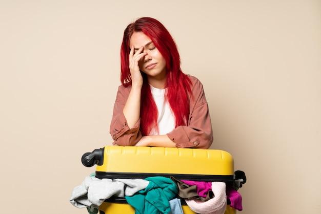 Reizigersmeisje met een kofferhoogtepunt van kleren op beige muur met hoofdpijn
