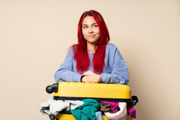 Reizigersmeisje met een kofferhoogtepunt van kleren op beige muur wordt geïsoleerd die twijfels hebben die terwijl omhoog het kijken die