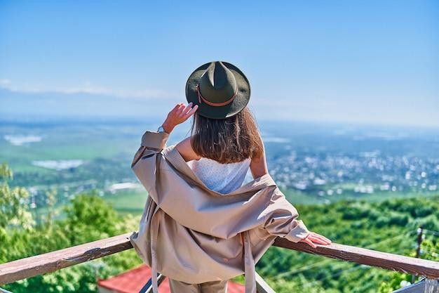 Reizigersmeisje met een vilten hoed die alleen staat en in de verte kijkt. genieten van een prachtig vrijheidsmoment van het leven en een serene rustige vredige kalme sfeer in de natuur. achteraanzicht