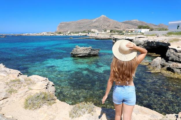 Reizigersmeisje met lang haar en hoed met kristallijne overzeese kustlijn op favignana, sicilië, italië