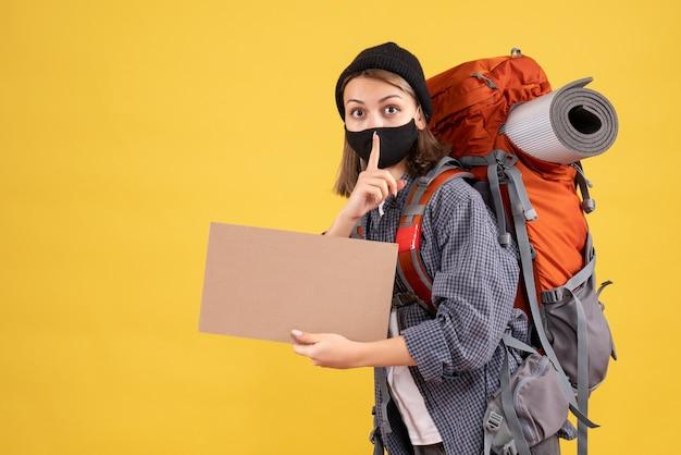 Reizigersmeisje met zwart masker en rugzak die karton vasthoudt en een stil teken maakt
