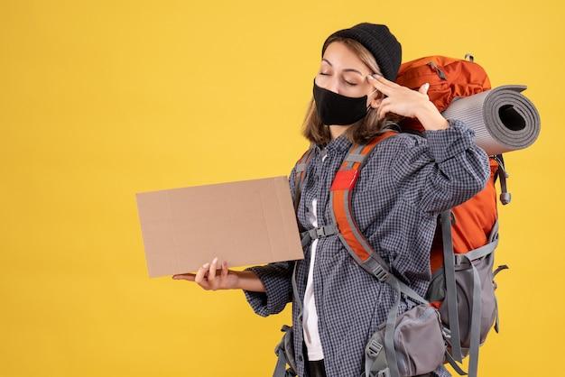 Reizigersmeisje met zwart masker en rugzak sluitende ogen met karton