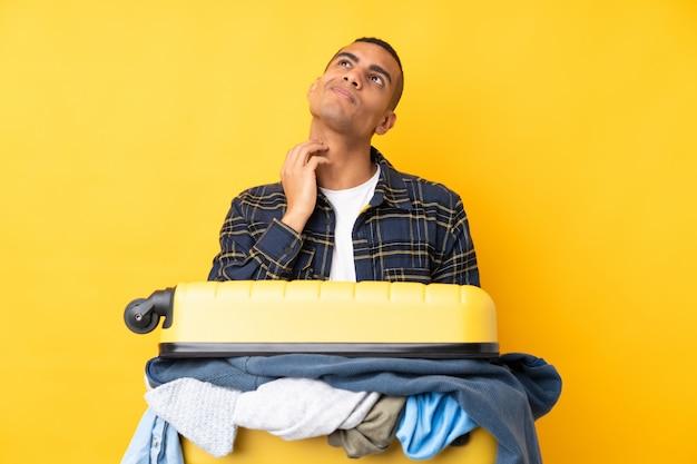 Reizigersmens met een kofferhoogtepunt van kleren over geïsoleerde gele muur die een idee denken