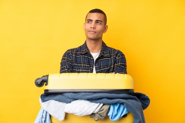 Reizigersmens met een kofferhoogtepunt van kleren over geïsoleerde gele muur die en zich aan de kant bevinden kijken