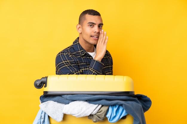 Reizigersmens met een kofferhoogtepunt van kleren over geïsoleerde gele muur die iets fluisteren