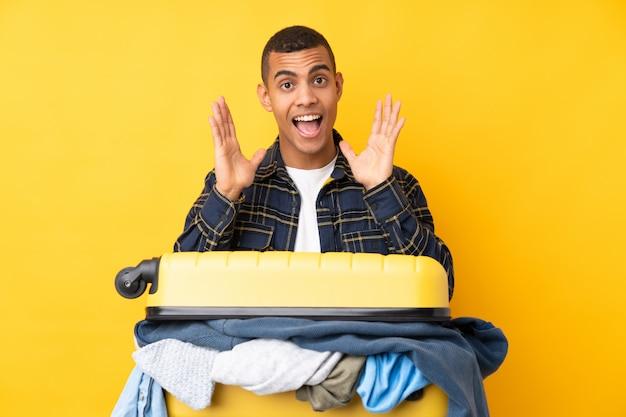 Reizigersmens met een kofferhoogtepunt van kleren over geïsoleerde gele muur met verrassingsgelaatsuitdrukking