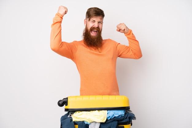 Reizigersmens met een kofferhoogtepunt van kleren over geïsoleerde witte muur die een overwinning vieren