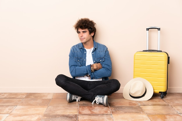 Reizigersmens zijn kofferzitting op de vloer die een idee denken