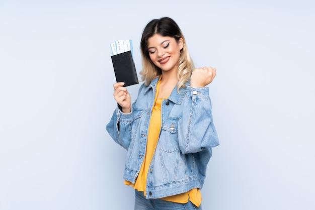 Reizigerstiener die een koffer op blauwe muur gelukkig in vakantie met paspoort en vliegtuigkaartjes houden