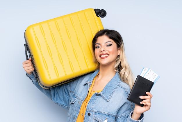 Reizigerstiener die een koffer op blauwe muur in vakantie met koffer en paspoort houden