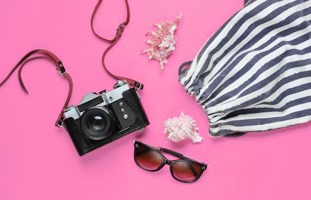 Reizigerstoebehoren met retro camera op roze