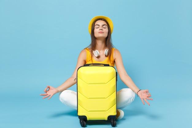 Reizigerstoeristenvrouw in gele vrijetijdskleding, hoed met kofferfotocamera op blauw
