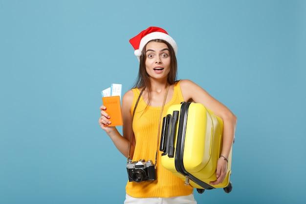 Reizigerstoeristenvrouw in kerstmuts, gele vrijetijdskleding met kaartjeszakcamera op blauw