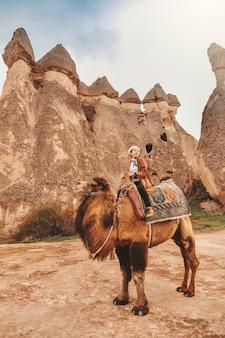 Reizigersvrouw berijdende kameel bij goreme-feeschoorstenen, cappadocia.