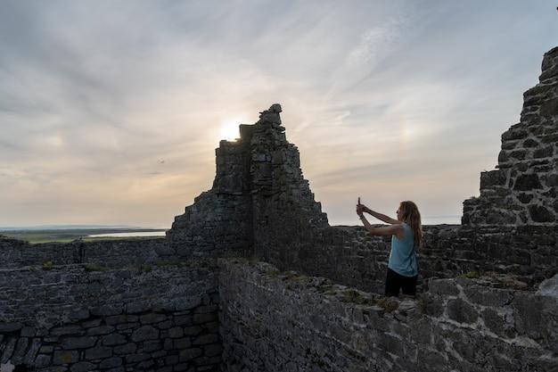 Reizigersvrouw bij o'dowd castle ireland die een foto maakt met mobiele telefoon