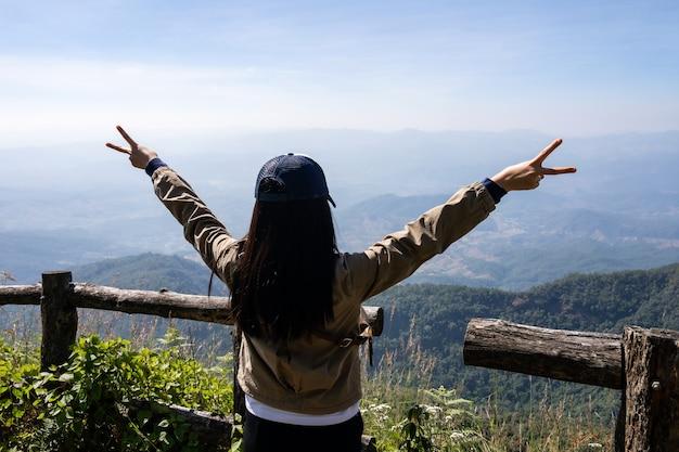 Reizigersvrouw die armen opent en overwinning v-teken toont in het midden van overvloedsbos