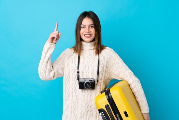 Reizigersvrouw die een gele koffer over geïsoleerde blauwe muur houden