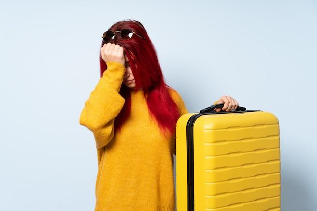 Reizigersvrouw die een koffer houden die op blauwe muur met hoofdpijn wordt geïsoleerd