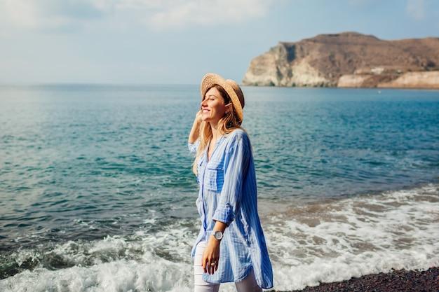 Reizigersvrouw die langs kust van rood strand lopen