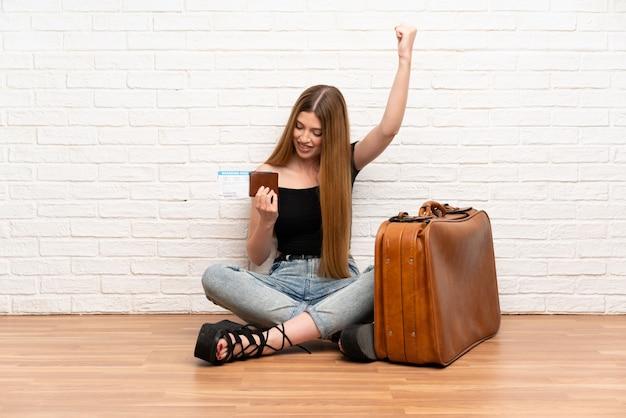 Reizigersvrouw die met koffer en instapkaart een overwinning vieren