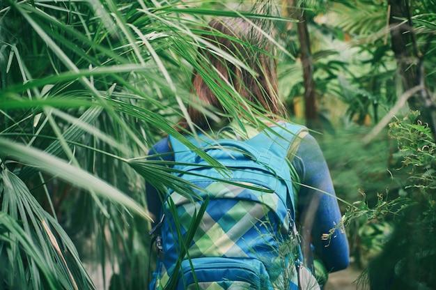 Reizigersvrouw die met rugzak op weg in het tropische bos lopen