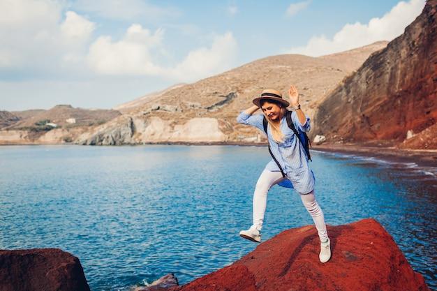 Reizigersvrouw die op rots op rood strand springen