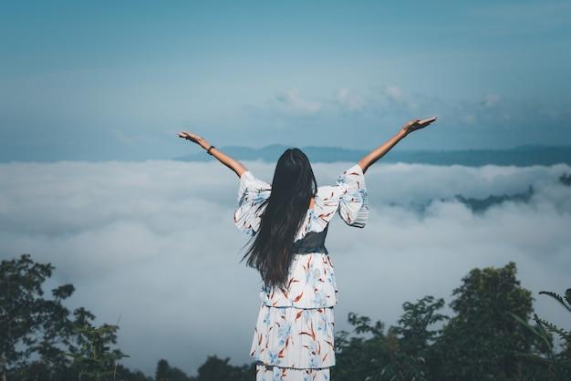 Reizigersvrouw die zich met opgeheven handen bevinden die mistig in de bergen bij zonsopgang kijken.