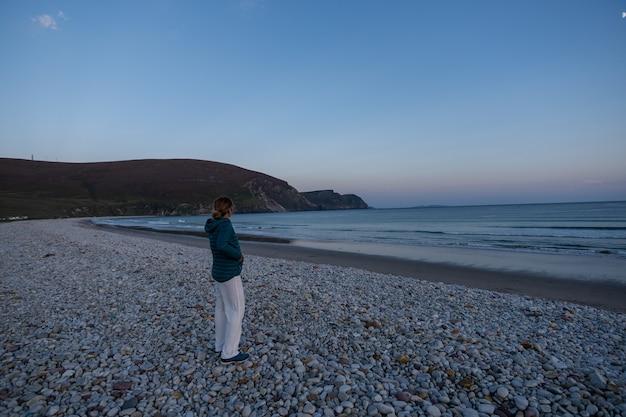 Reizigersvrouw die zonsondergang op rotsachtig strand bewonderen